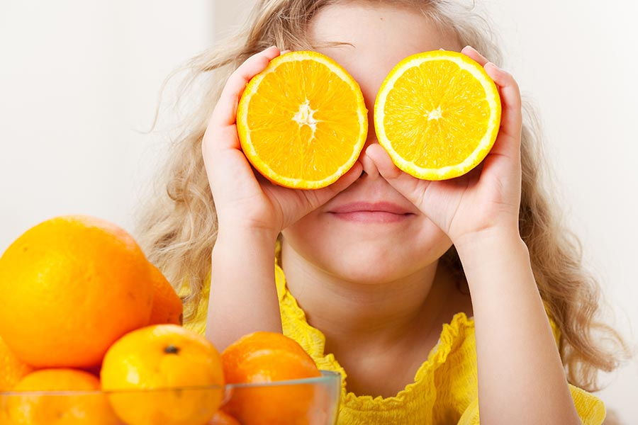 Early Care & Education Nutrition Services Little Girl with Oranges